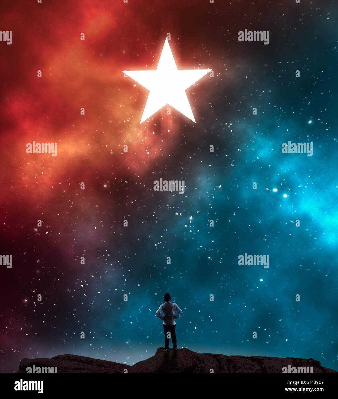 Young man looking at a star during night on a colorful nebula . Stock Photo