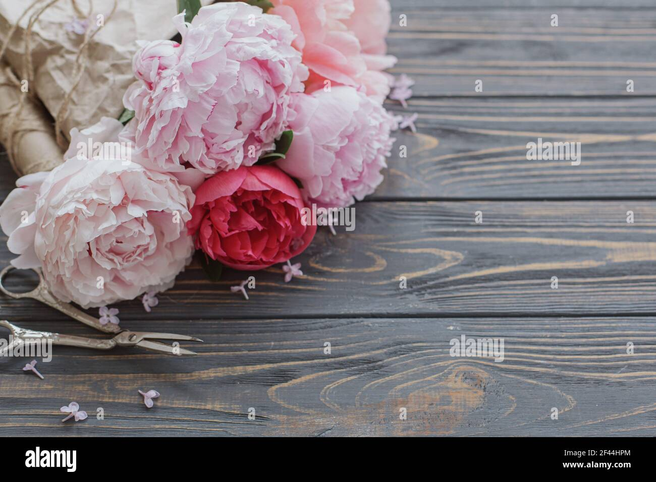 Beautiful stylish peony bouquet in paper, twine and scissors on rustic dark wooden background, copy space. Happy Mothers day greetings. Pink and white Stock Photo