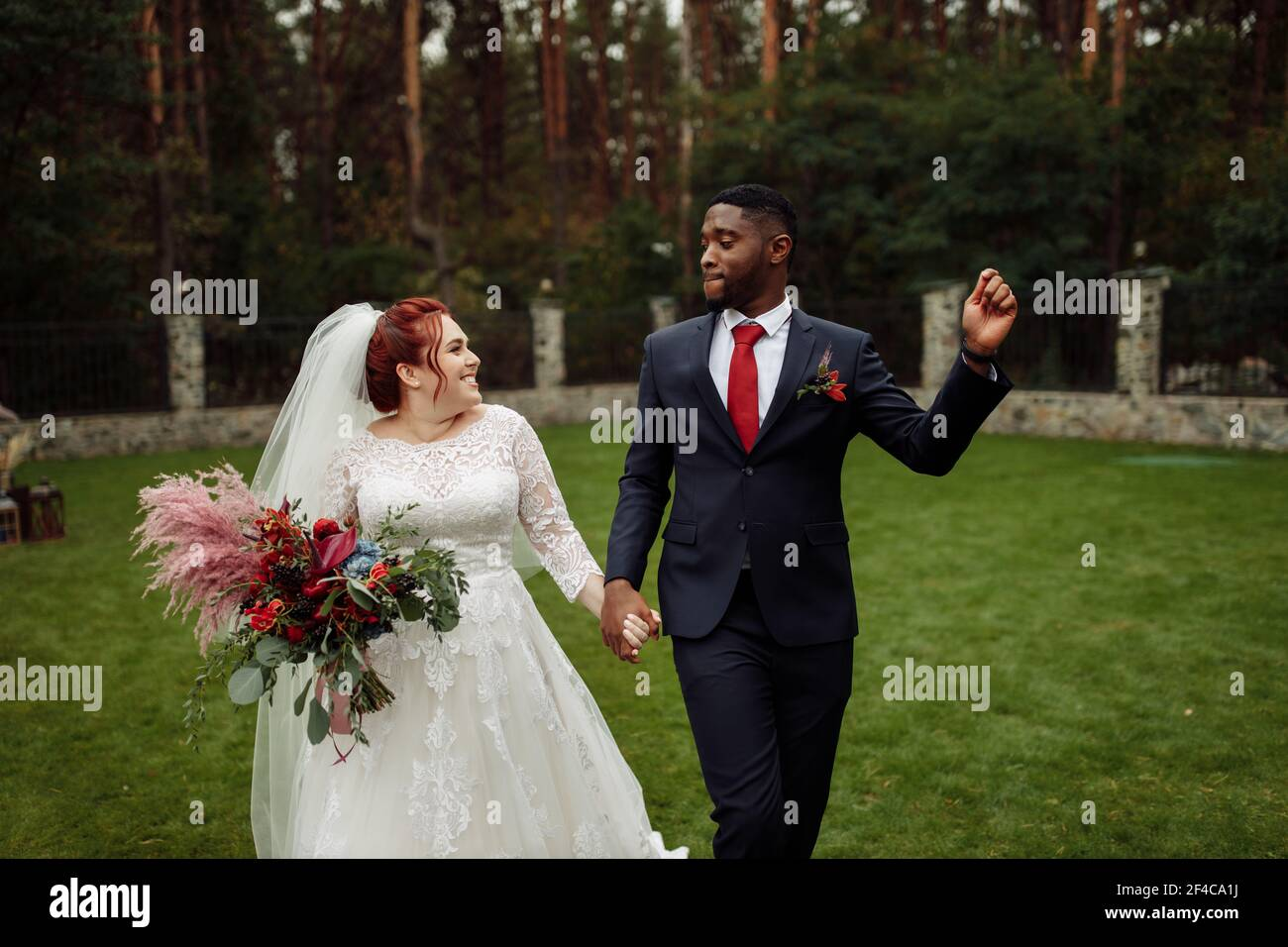 https://c8.alamy.com/comp/2F4CA1J/joyful-couple-walking-at-the-park-handsome-african-american-man-with-lovely-white-woman-on-wedding-day-beautiful-bride-with-charming-groom-enjoy-2F4CA1J.jpg