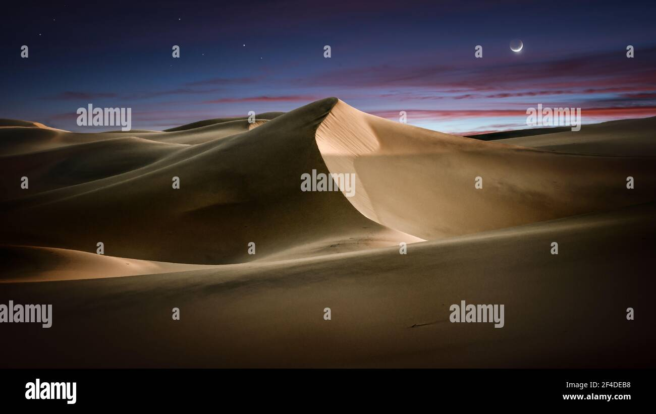 Dramatic sky over Mesquite Flat sand dunes at sunrise, Death Valley, California, USA Stock Photo