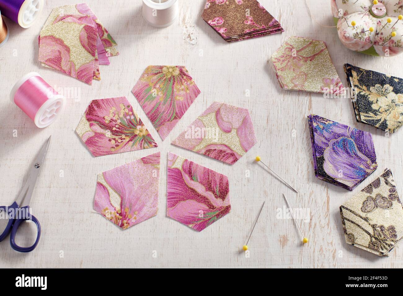 Pentagonal pieces of fabric lying in the shape of a flower, stacks of multi-colored pieces of fabric, sewing accessories on a white surface Stock Photo