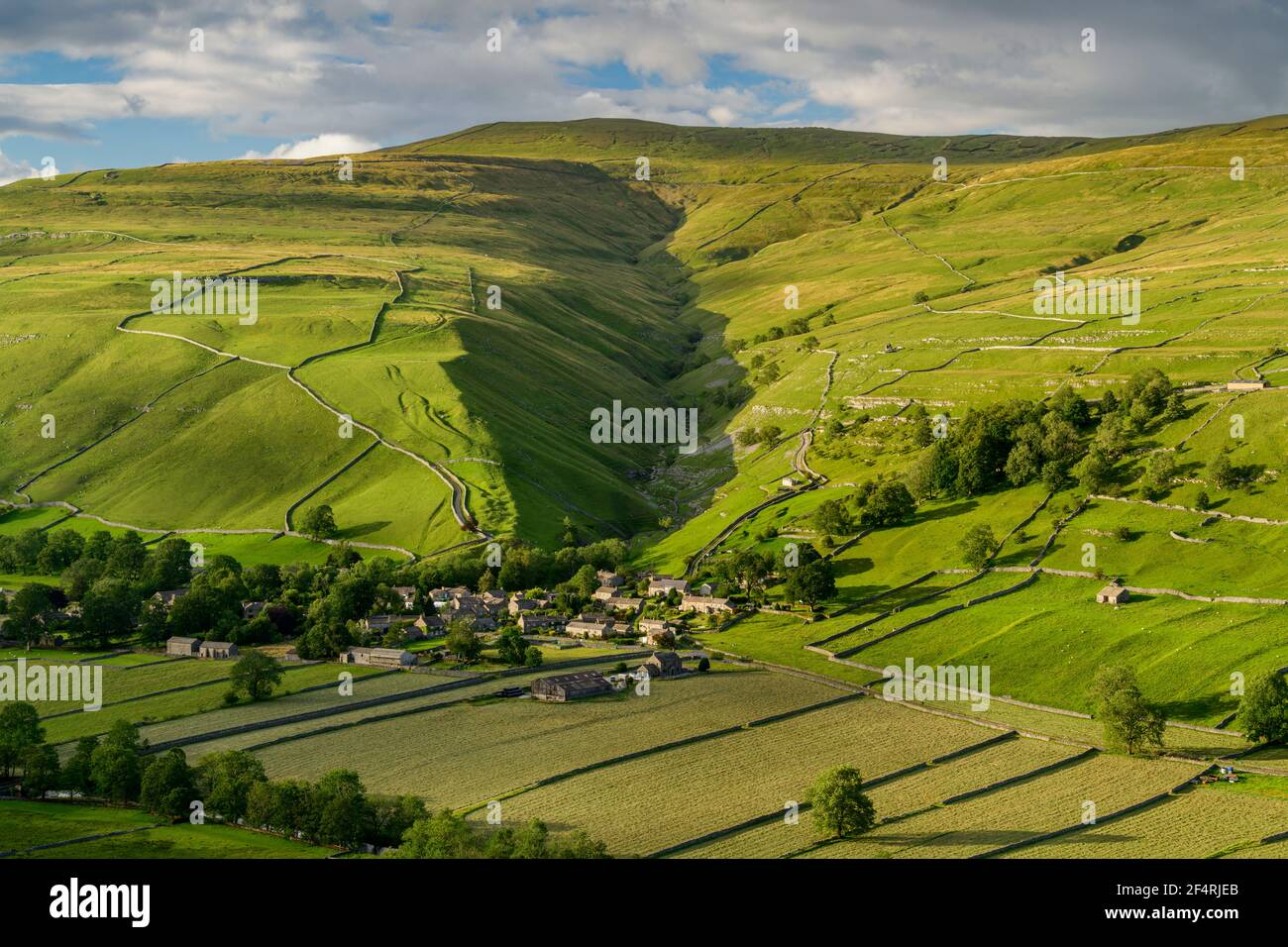 Scenic Dales village (houses) nestling in valley by dry-stone walls, hillside slopes & steep-sided Cam Gill gorge - Starbotton, Yorkshire England, UK. Stock Photo