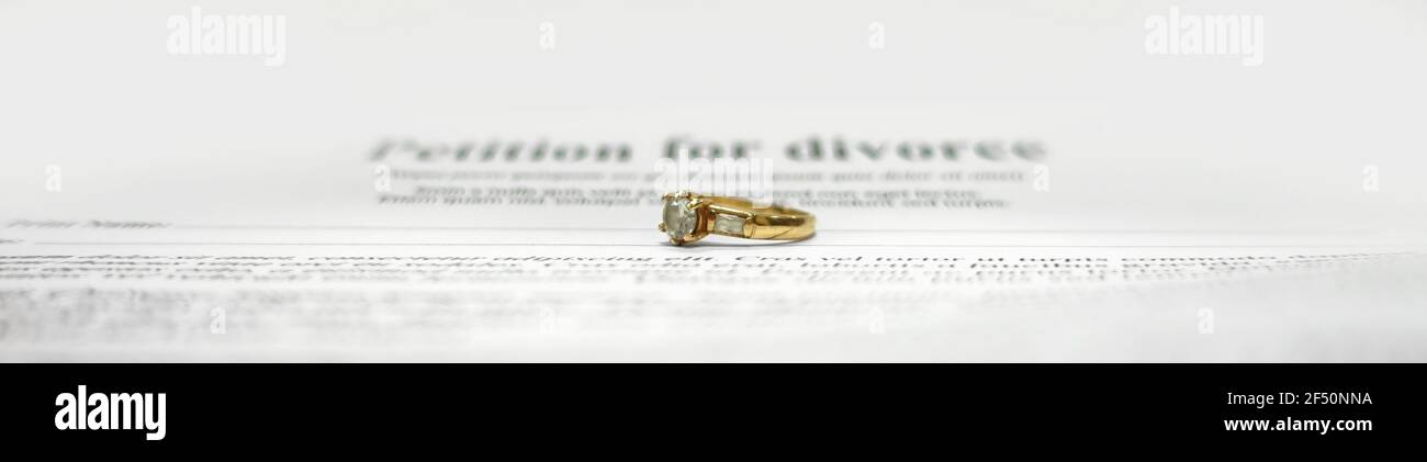 Conceptual image for divorce with two golden wedding rings in the middle and petition for divorce as background. Main focus on the rings. Stock Photo