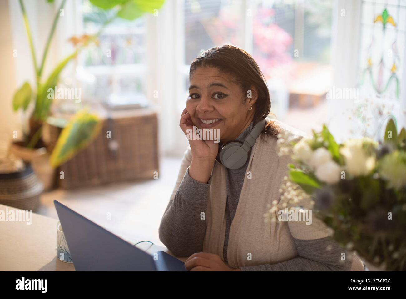Portrait happy woman working from home at laptop Stock Photo