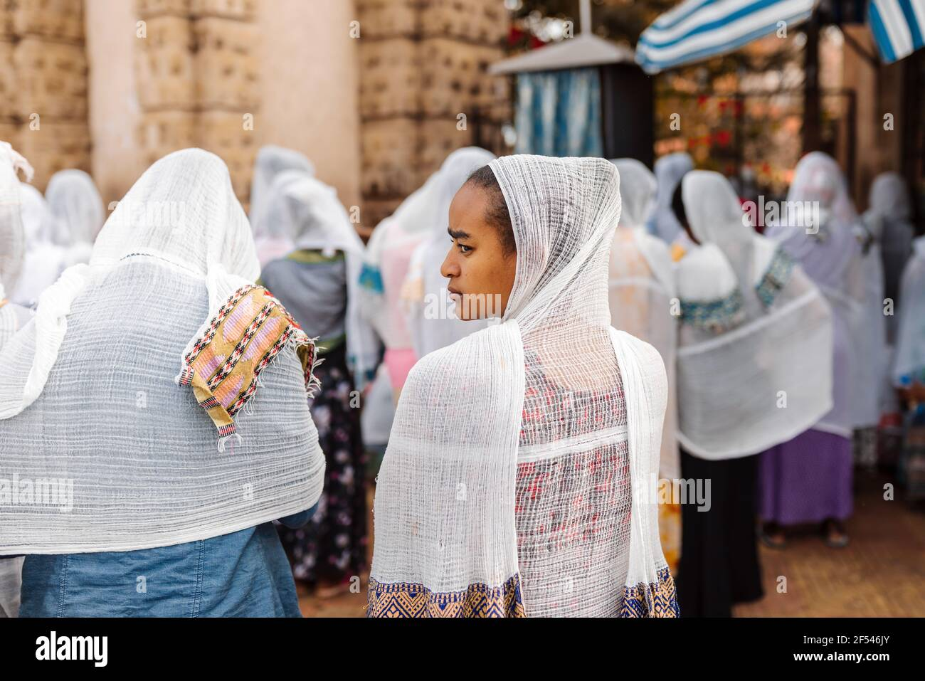 Azezo, Amhara Region, Ethiopia - April 21, 2019: Orthodox Christian people white dressed walk to mass on the street during easter holiday. Bahir Dar, Stock Photo