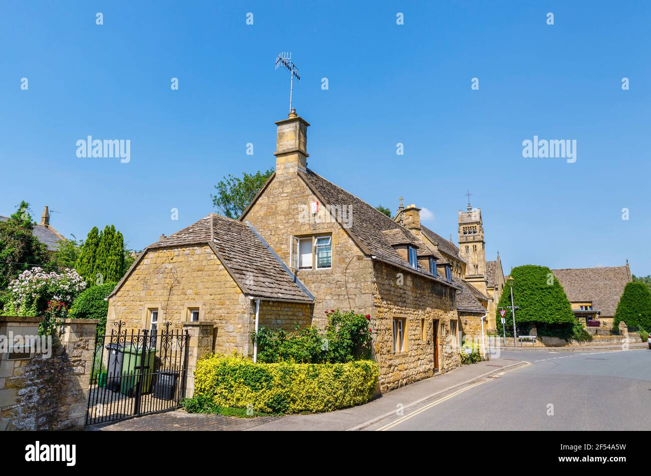 Typical roadside Cotswold stone slate roof houses and St Catharine's Church in Chipping Campden, a small market town in the Cotswolds, Gloucestershire Stock Photo