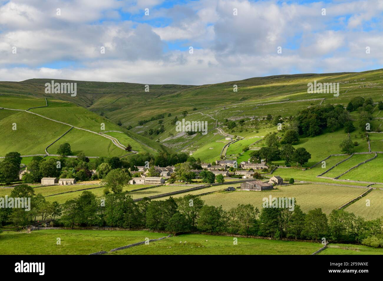 Picturesque Dales village (stone houses) nestling in sunlit valley by fields, hills, hillsides & steep-sided gorge - Starbotton, Yorkshire England UK. Stock Photo