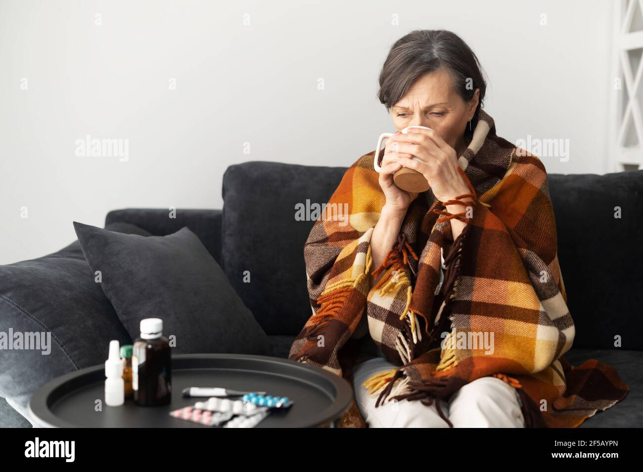 Home alone hot women A Senior Woman Feels Unwell Sits Down On The Couch Alone At Home Covered With Blanket Feels Chill An Elderly Woman Suffers From Viral Disease Has Fever Treats Herself With Hot Remedy