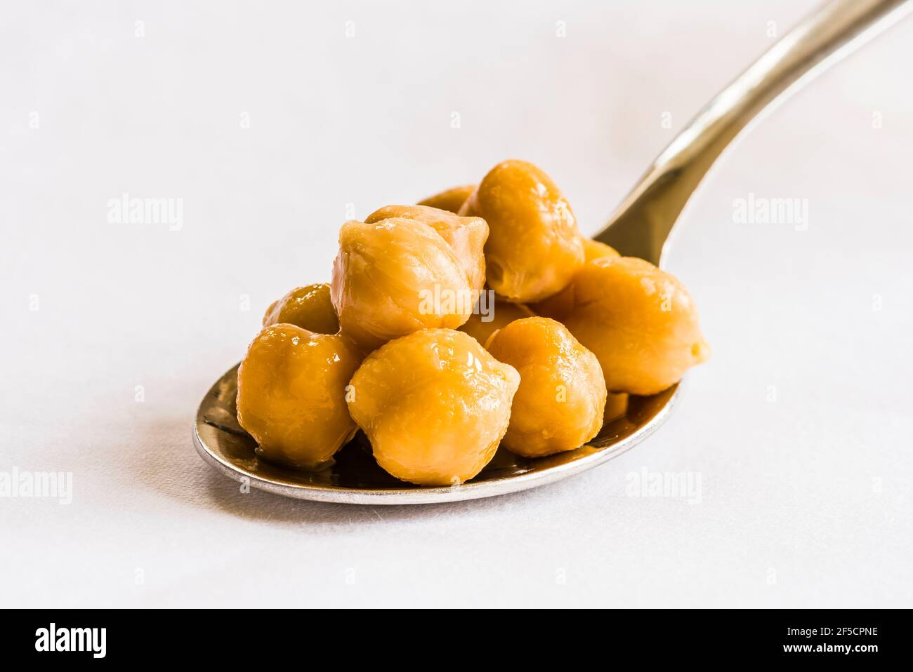 Close-up of chickpeas on a silver spoon on a white tablecloth, London, UK Stock Photo