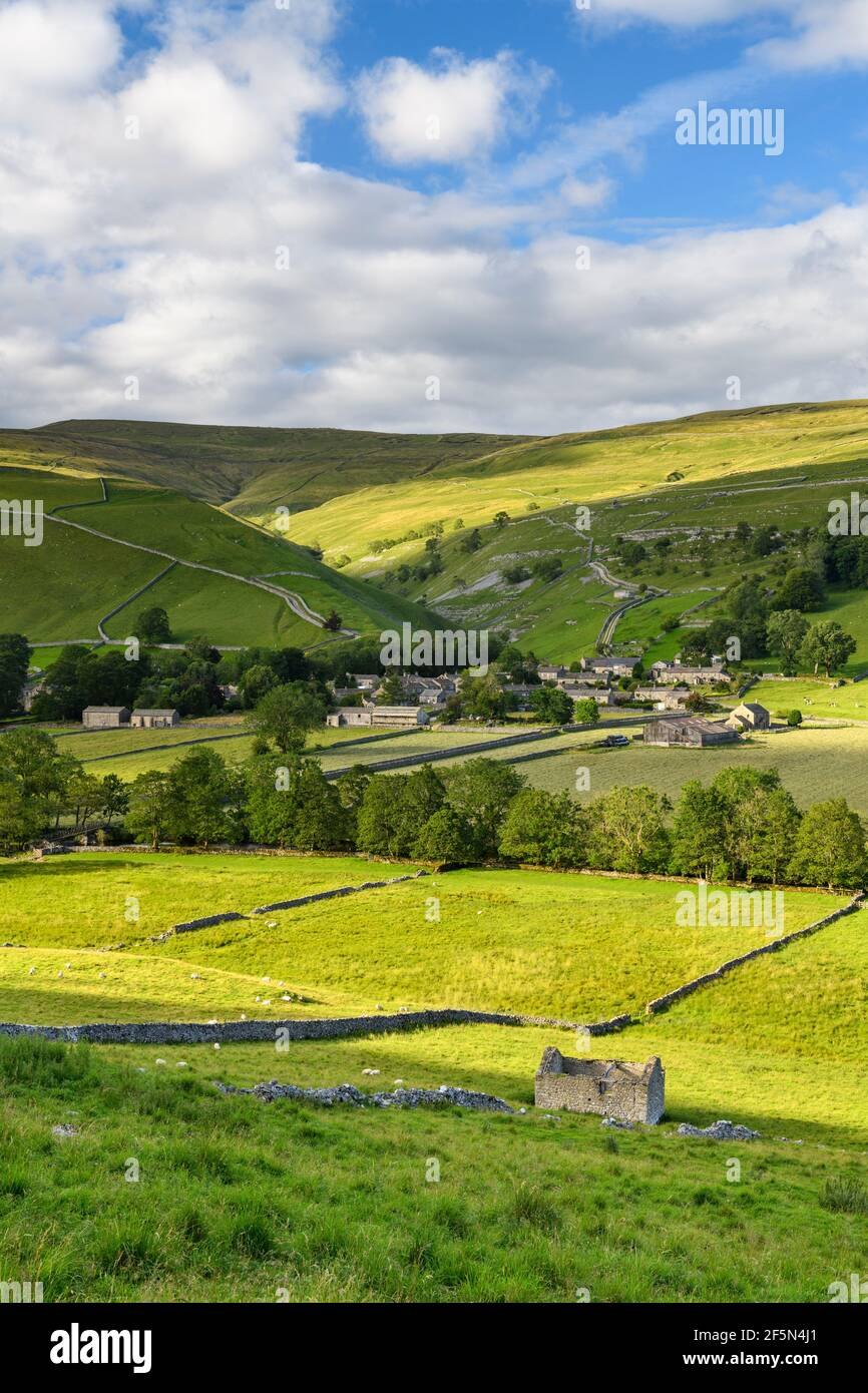 Picturesque Dales village houses, nestling in sunlit valley, fields, hills, hillsides, field walls & old barn ruin - Starbotton, Yorkshire England UK. Stock Photo