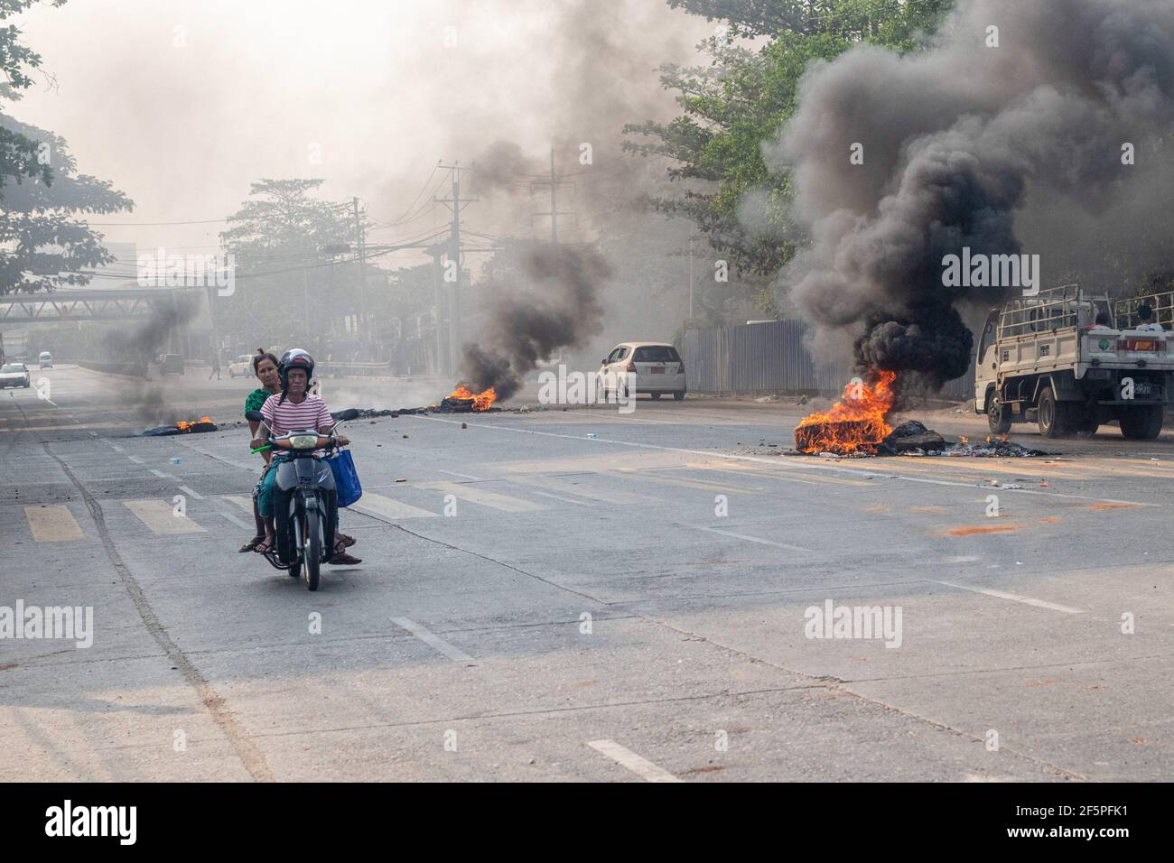 A motorcyclist rides past burning tires on the street during a protest against the military coup.Myanmar police and military soldiers (tatmadow) attacked protesters with rubber bullets, live ammunition, tear gas and stun bombs in response to anti-military coup protesters on Saturday, killing more than 90 people and injured many others. At least 300 people have been killed in Myanmar since the 1 February coup, a UN human rights official has said. Myanmar's military detained State Counsellor of Myanmar Aung San Suu Kyi on February 01, 2021 and declared a state of emergency while seizing the powe Stock Photo