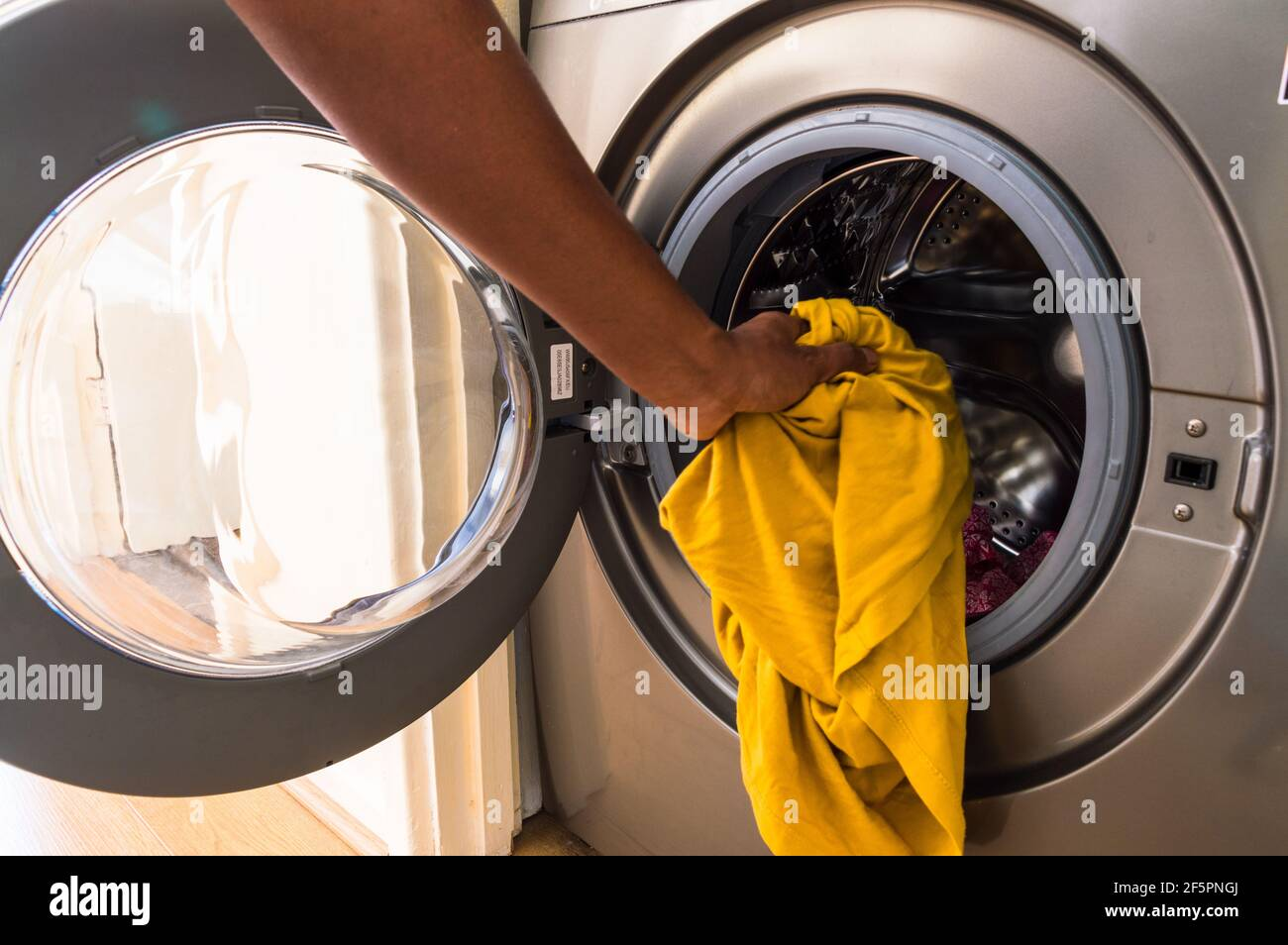 Adult middle aged Asian man loading washing machine with soiled clothes Stock Photo