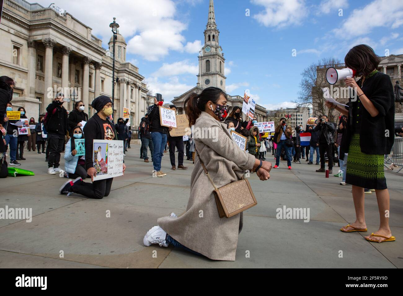 A protester speaks to colleagues through a megaphone while kneeling holding placards expressing their opinion during a peaceful demonstration.Myanmar anti military coup protesters gathered at Trafalgar Square as dozens more are killed in the country. Myanmar police and military soldiers (tatmadow) attacked protesters with rubber bullets, live ammunition, tear gas and stun bombs in response to anti-military coup protesters on Saturday in Myanmar, killing more than 90 people and injured many others. At least 300 people have been killed in Myanmar since the 1 February coup, a UN human rights off Stock Photo