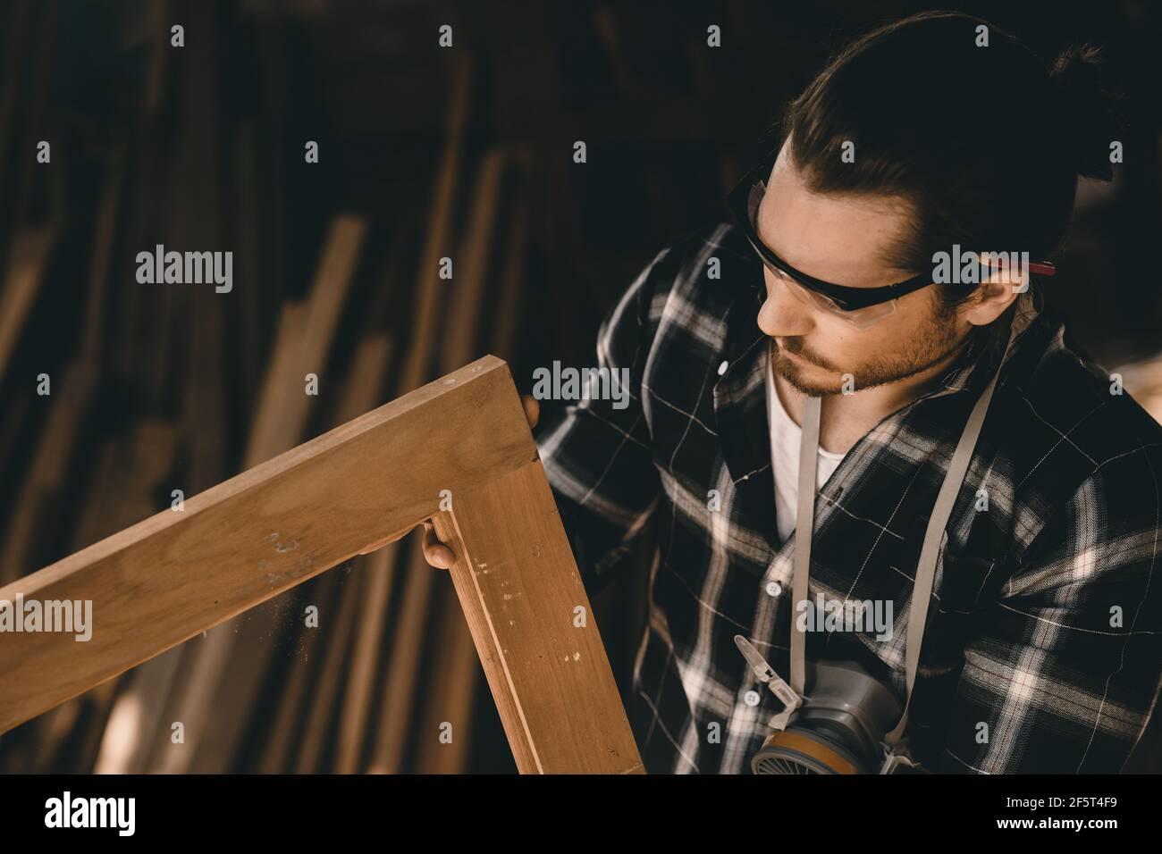 Carpenter man professional skilled in wood work looking detail of masterpiece woodcraft in furniture workshop Stock Photo