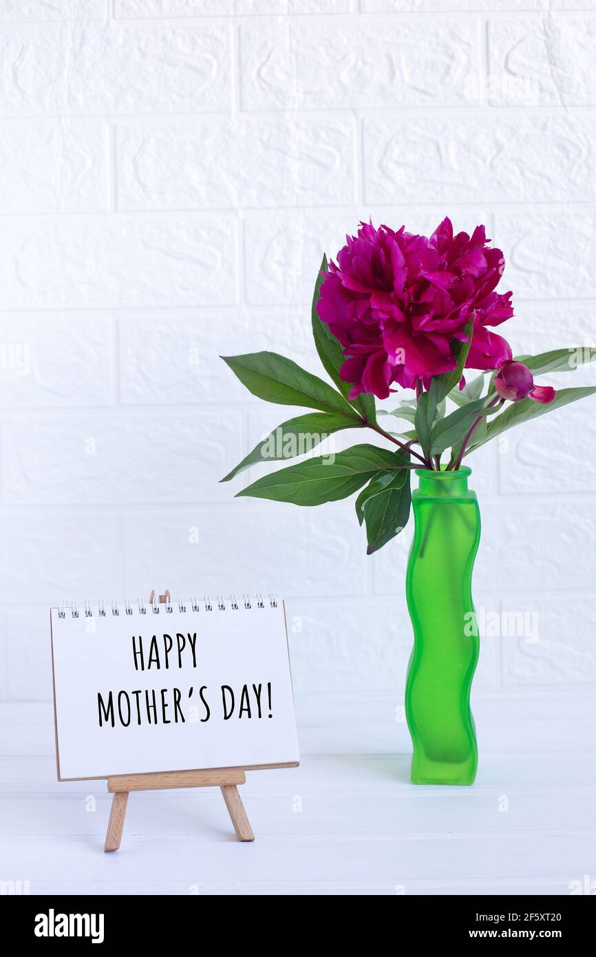 Happy Mothers day text written on notebook and one peony in vase. greeting card Stock Photo