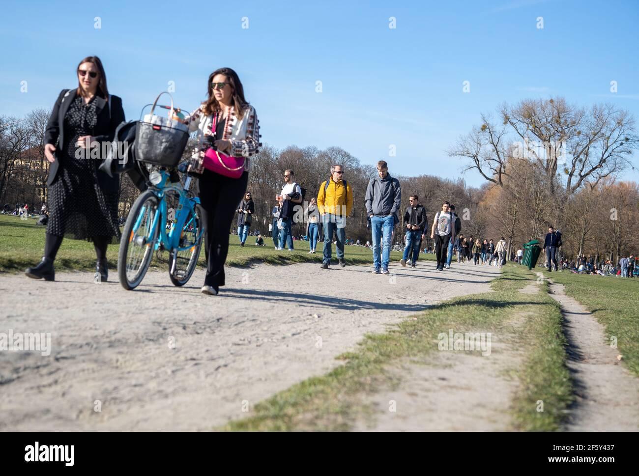 Viele Menschen gehen an einem schönen Sonntag Nachmittag am 28.3.2021 in den Englischen Garten in München. Coronavirus Inzidenz beträgt aktuell 98, 8. Sollte die Inzidenz an drei Tagen über 100 liegen, so tritt die Notbremse in Kraft, so dass die Öffnungen müssen zurückgezogen werden und eine nächtliche Ausgangssperre tritt in Kraft. - Many people on a sunny sunday afternoon go to the English Garten in Munich Germany on March 28. The Covid-19 incidence is 98.8. if it will rise above 100 heavy measures such as a complete lockdown during the night. (Photo by Alexander Pohl/Sipa USA) Stock Photo