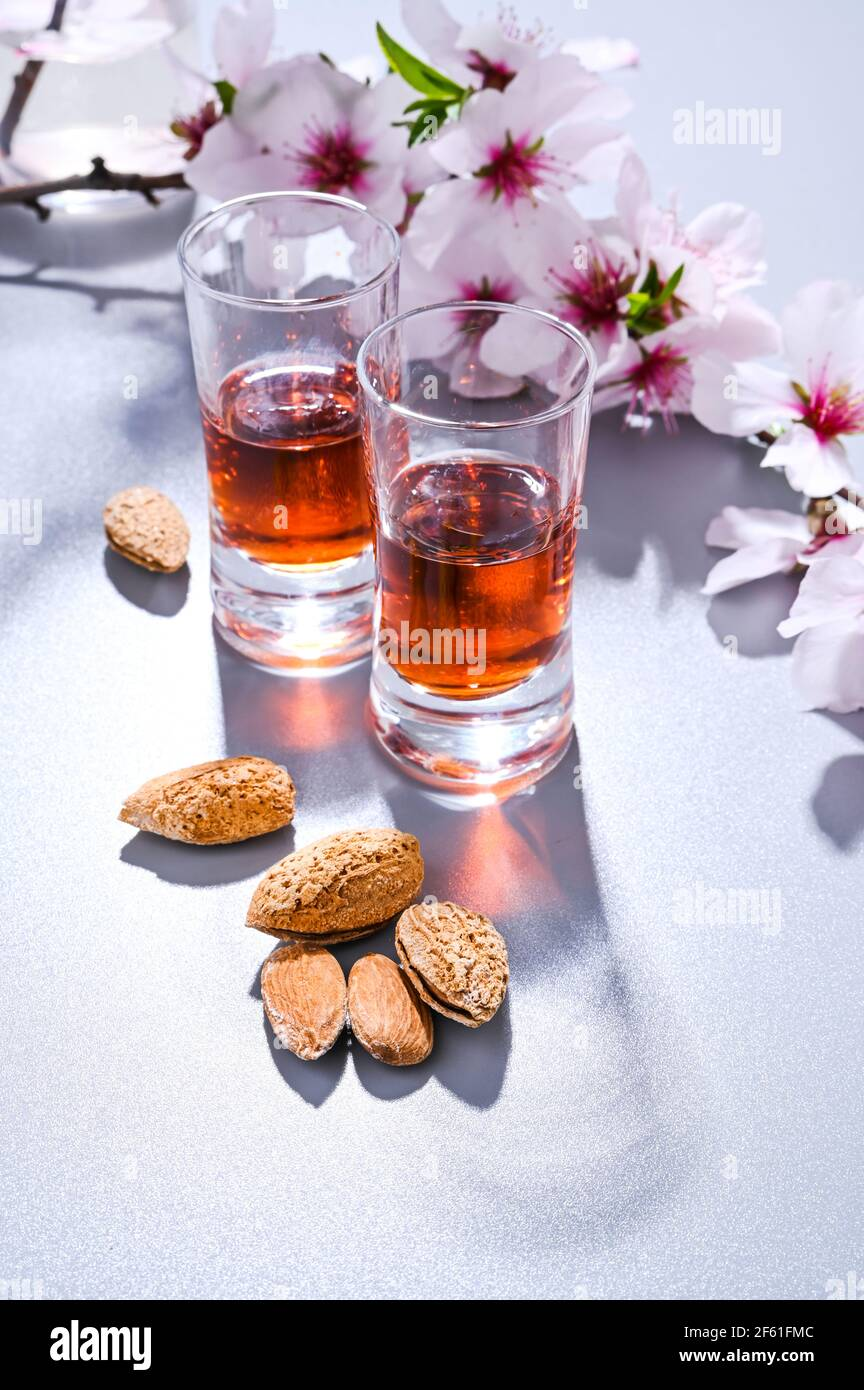 almond liquor. The traditional strong drink in italy to complete the dinner is a liqueur made from nuts and berries. Ratafia, alcohol in shot. top view on the table and blooming almonds. Copy space Stock Photo
