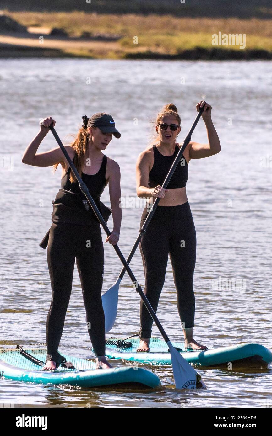 Two female holidaymakers standing on Stand Up Paddleboards and paddling up the Gannel River in Newquay in Cornwall. Stock Photo