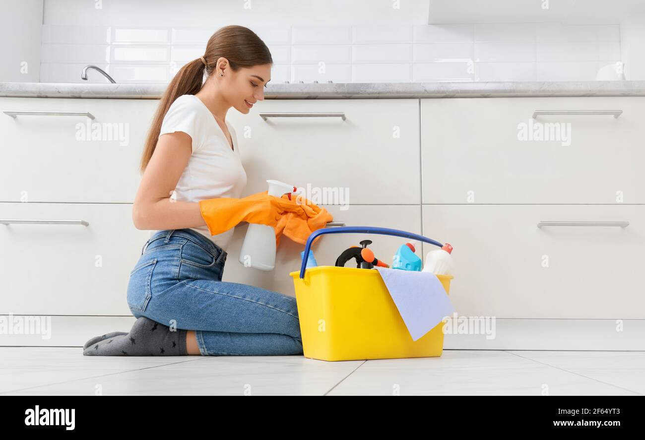 Beautiful woman in protective gloves cleaning kitchen with special detergent. Concept of cleaning modern bright kitchen. Stock Photo