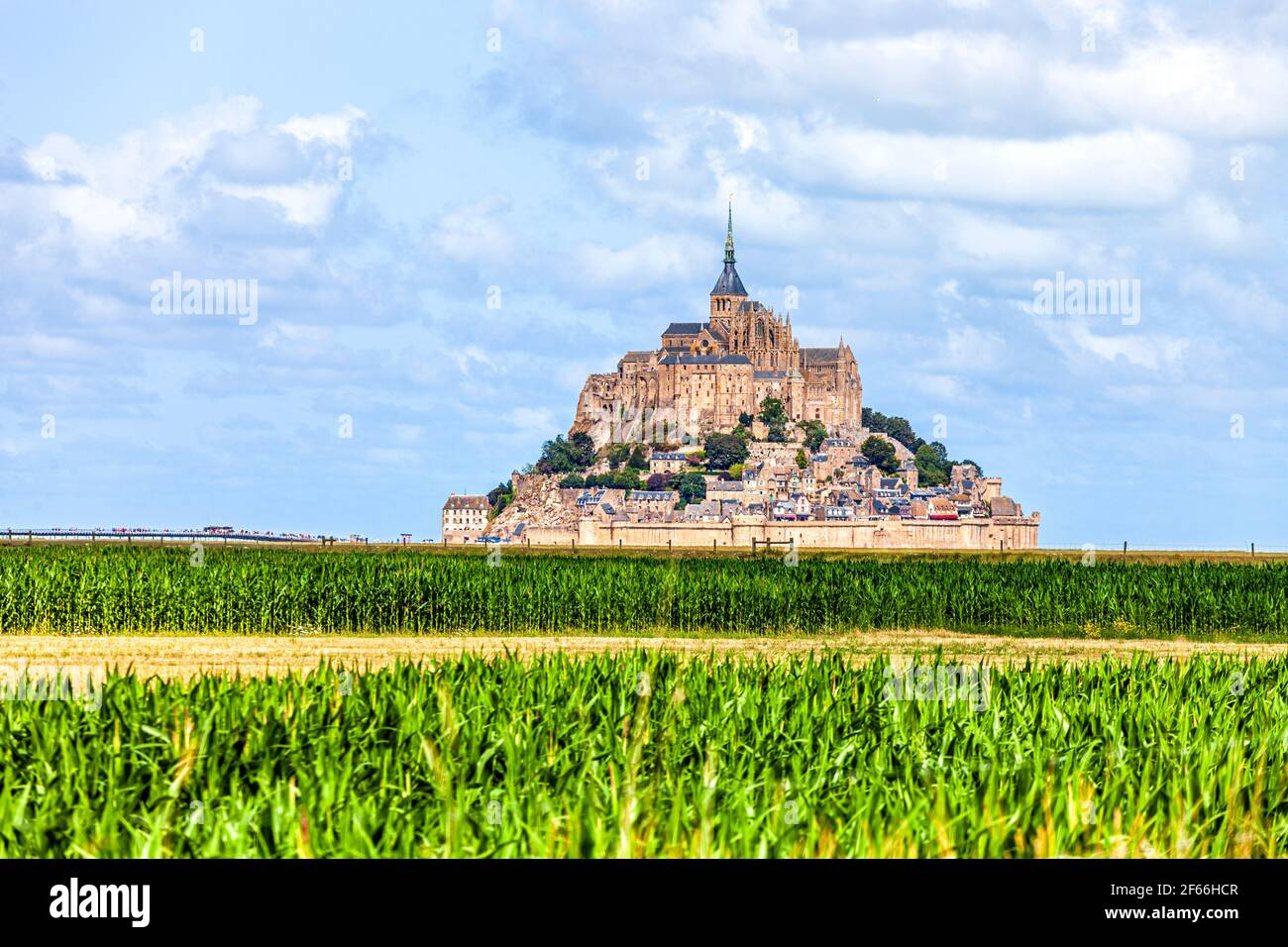 View of famous historic Le Mont Saint-Michel tidal island with green corn fields infront Stock Photo
