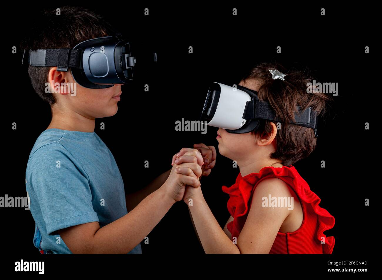 A caucasian boy and a girl wearing virtual reality headsets are playing multiplayer game. A futuristic concept with kids being in a different dimensio Stock Photo