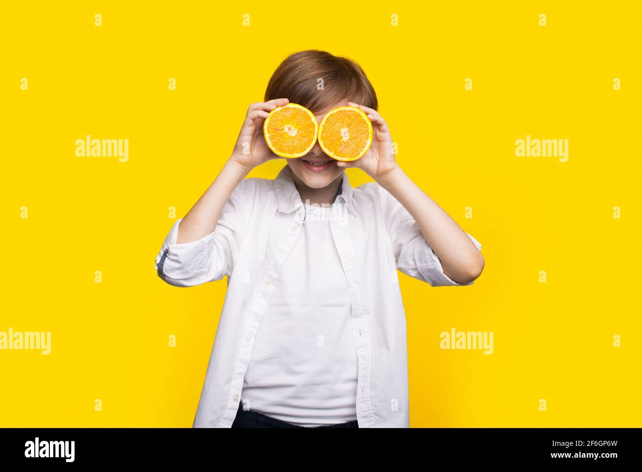 Caucasian boy is covering his eye with sliced lemons smiling on a yellow studio wall Stock Photo