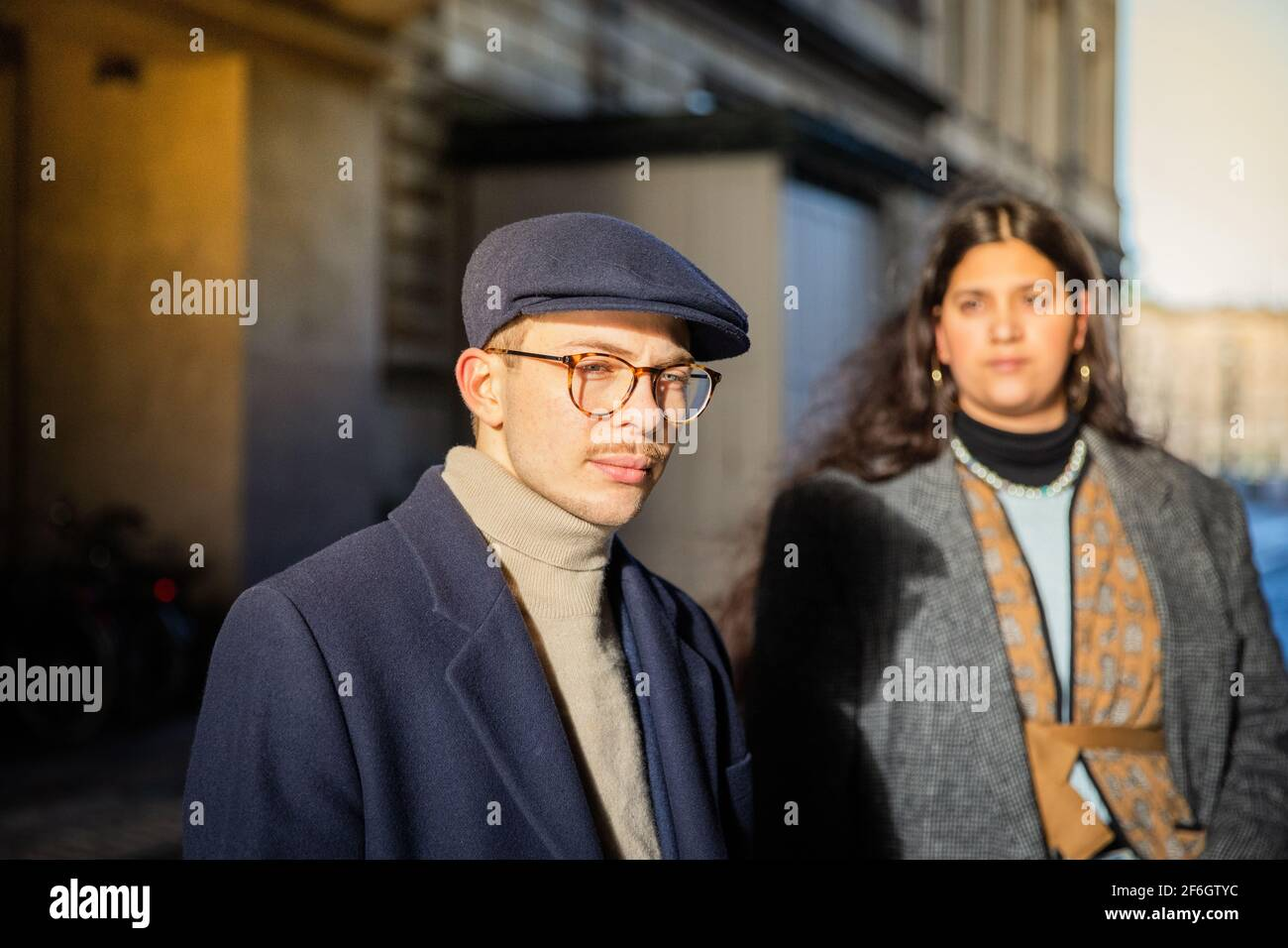 Portrait of a serious and elegant young guy wearing a flat cap. Her friend is out of focus behind. Youth and diversity concept Stock Photo