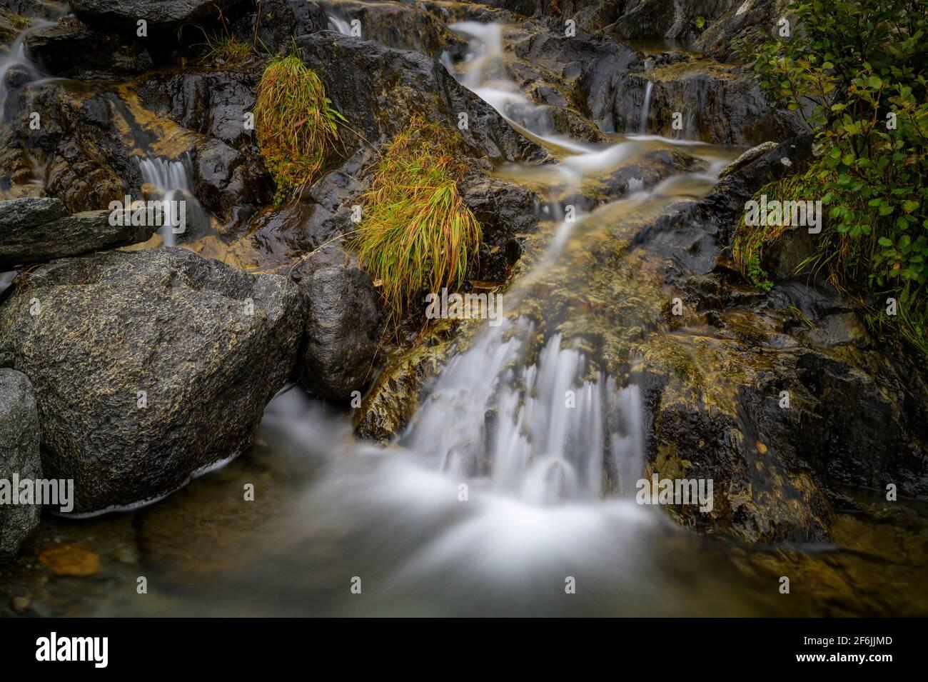 Small waterfall in mountain creek, Oberalppass, Switzerland Stock Photo