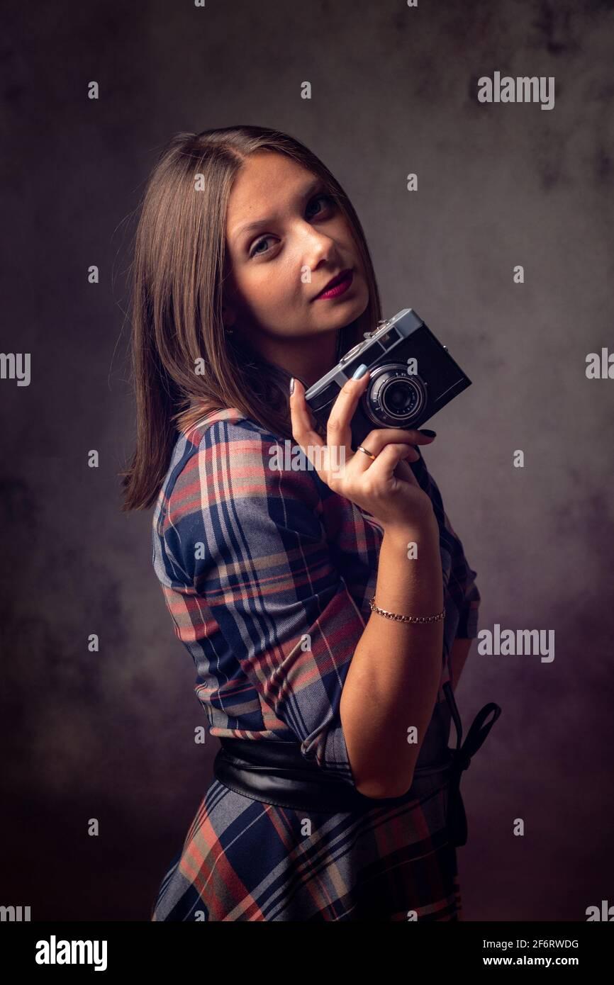 Girl photographer with retro camera, studio photography on gray background. Stock Photo