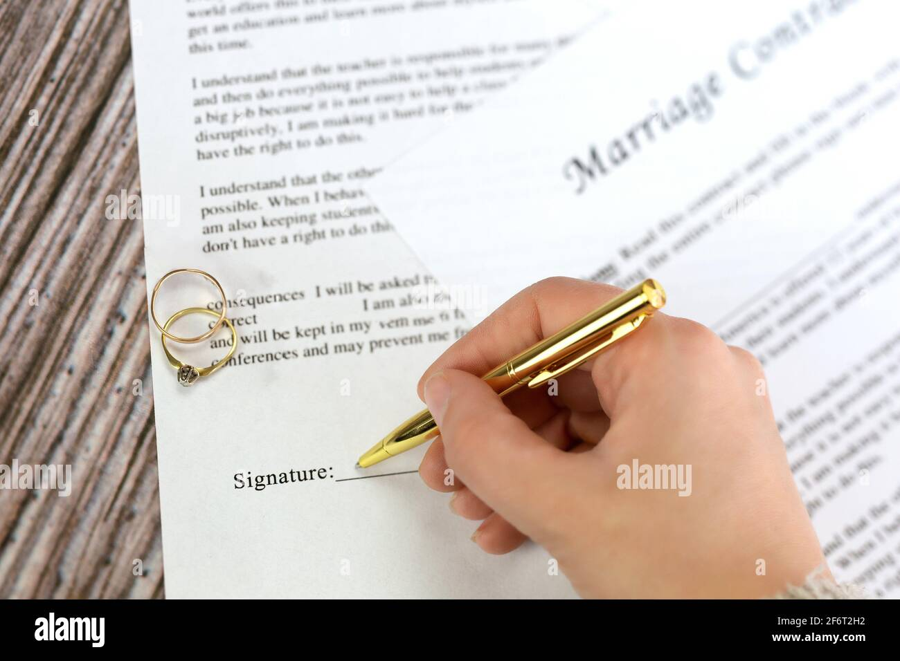 Marriage contract with two golden wedding rings and gold pen, prenuptial agreement, macro close up, sign with signanture,document,agreement concept Stock Photo