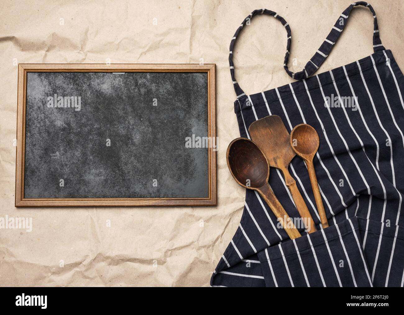 blank square wood frame and blue chef apron, top view, copy space. Stock Photo