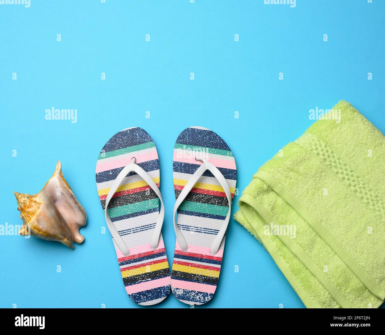 rubber womens striped slippers on a blue background, top view, place for an inscription. Stock Photo
