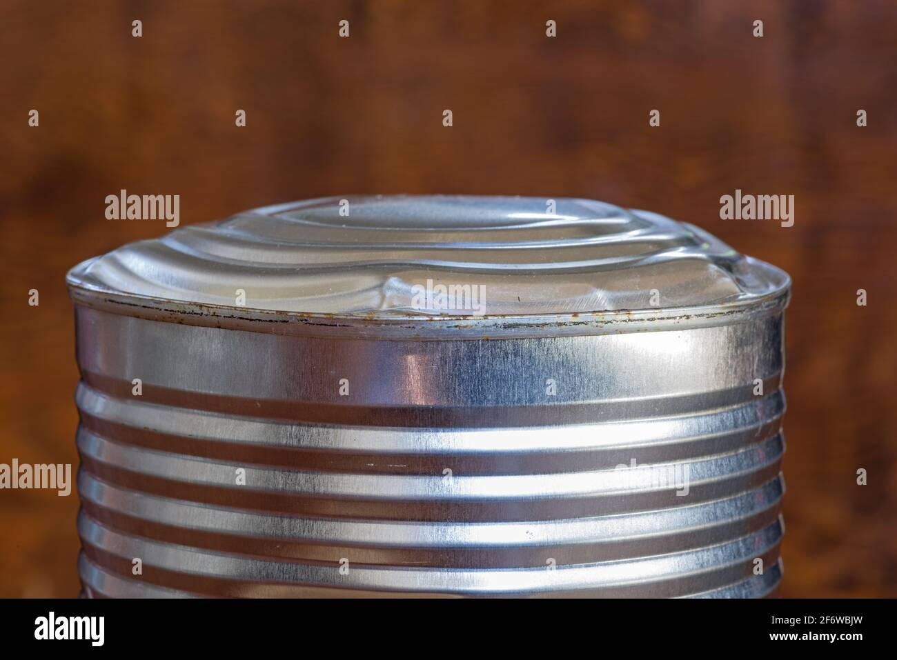 bulging old food can end indicating spoiled contents Stock Photo
