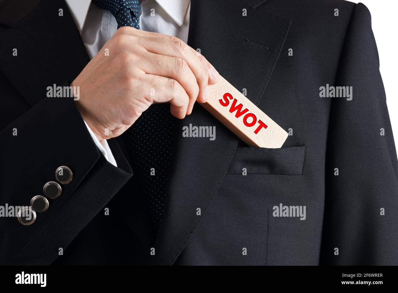 Businessman takes out a wooden block from his pocket with the word SWOT. Business marketing swot analysis concept. Stock Photo