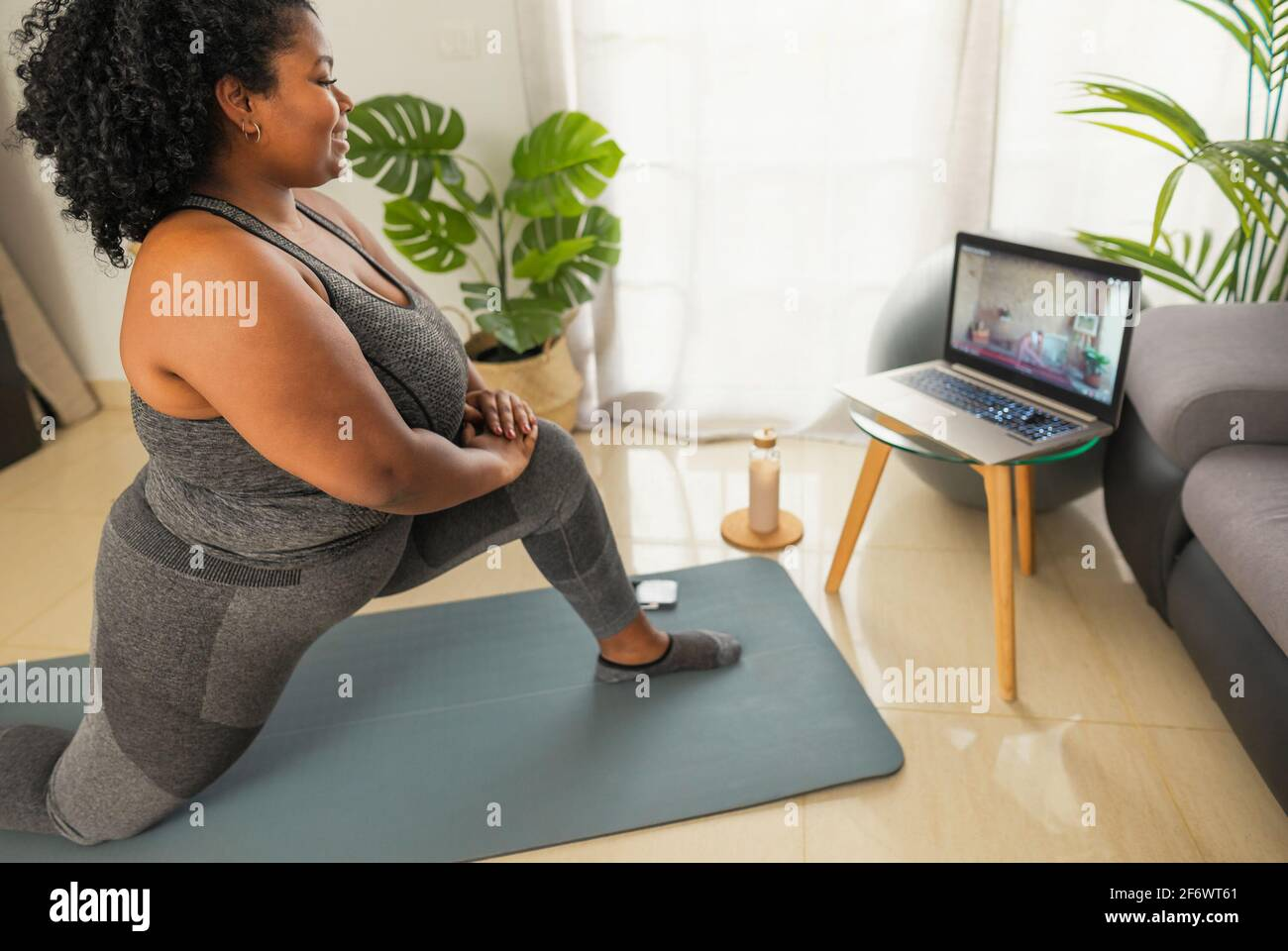 Young African woman doing pilates virtual fitness class with laptop at home - Sport wellness people lifestyle concept Stock Photo