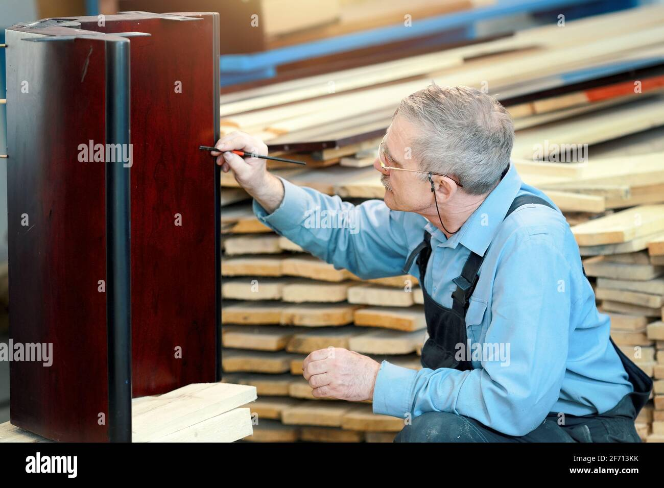 An elderly man with glasses and gray hair works with wood in a carpentry shop. A worker of Caucasian appearance is engaged in the restoration of furniture. Part-time job for a pensioner Stock Photo