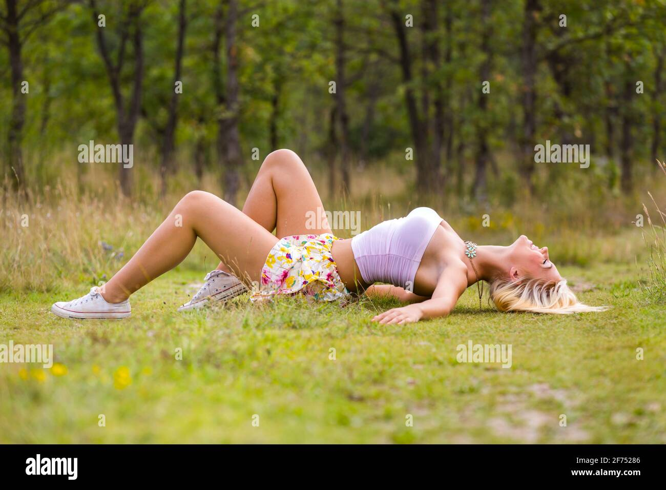 Teengirl Green nature forest trees natural environment countryside country countrygirl lying on her back stretching stretch overstretching tensioning Stock Photo
