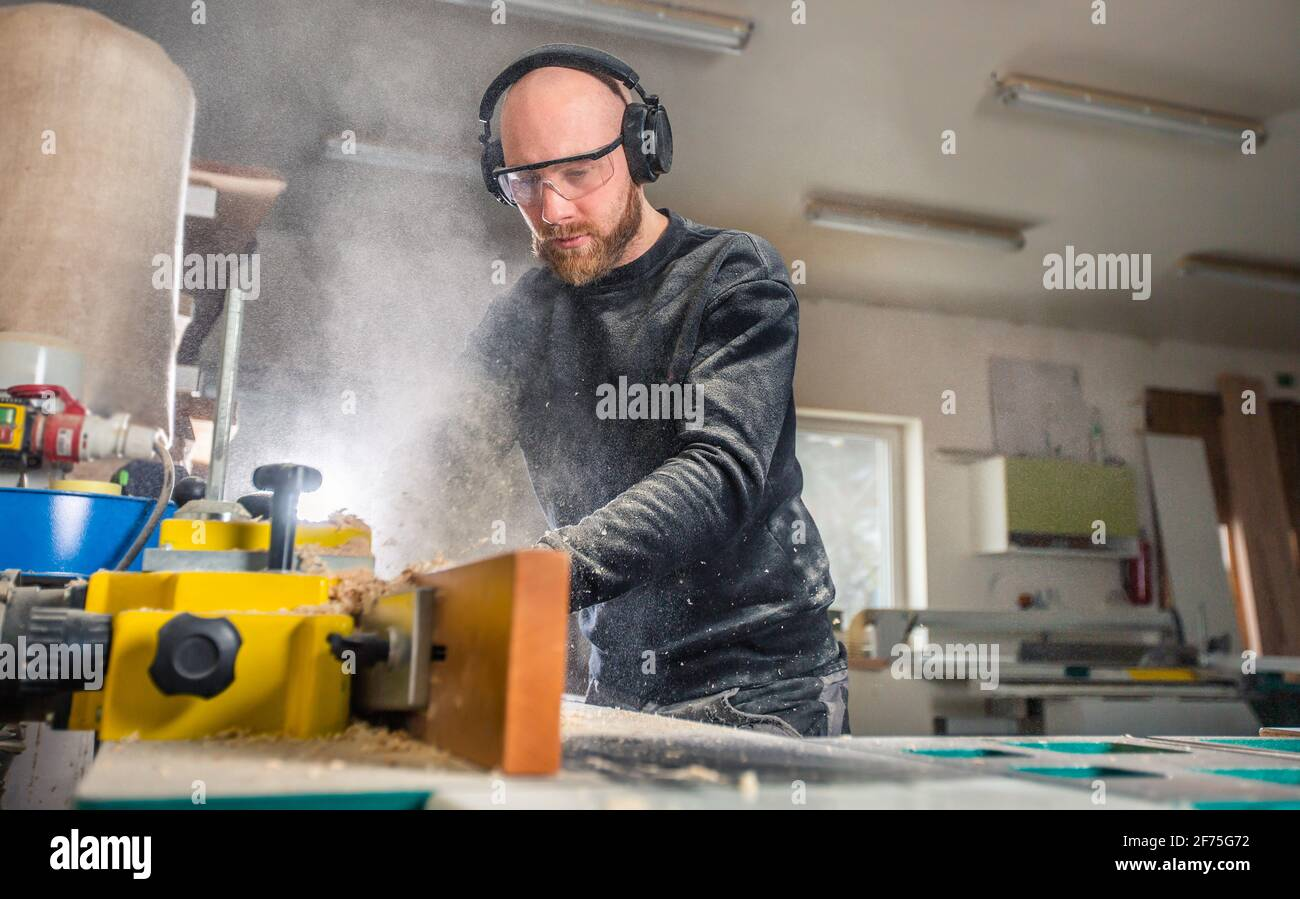 Carpenter working on woodworking saw machines in carpentry shop, industrial concept Stock Photo