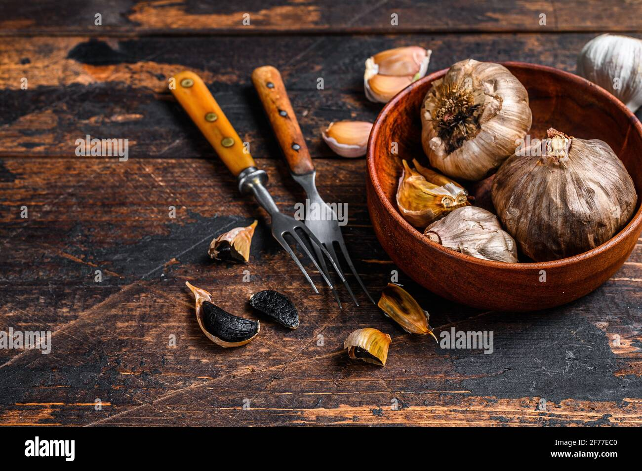 Bulbs and cloves of fermented black garlic in a plate. Dark wooden background. Top view. Copy space Stock Photo