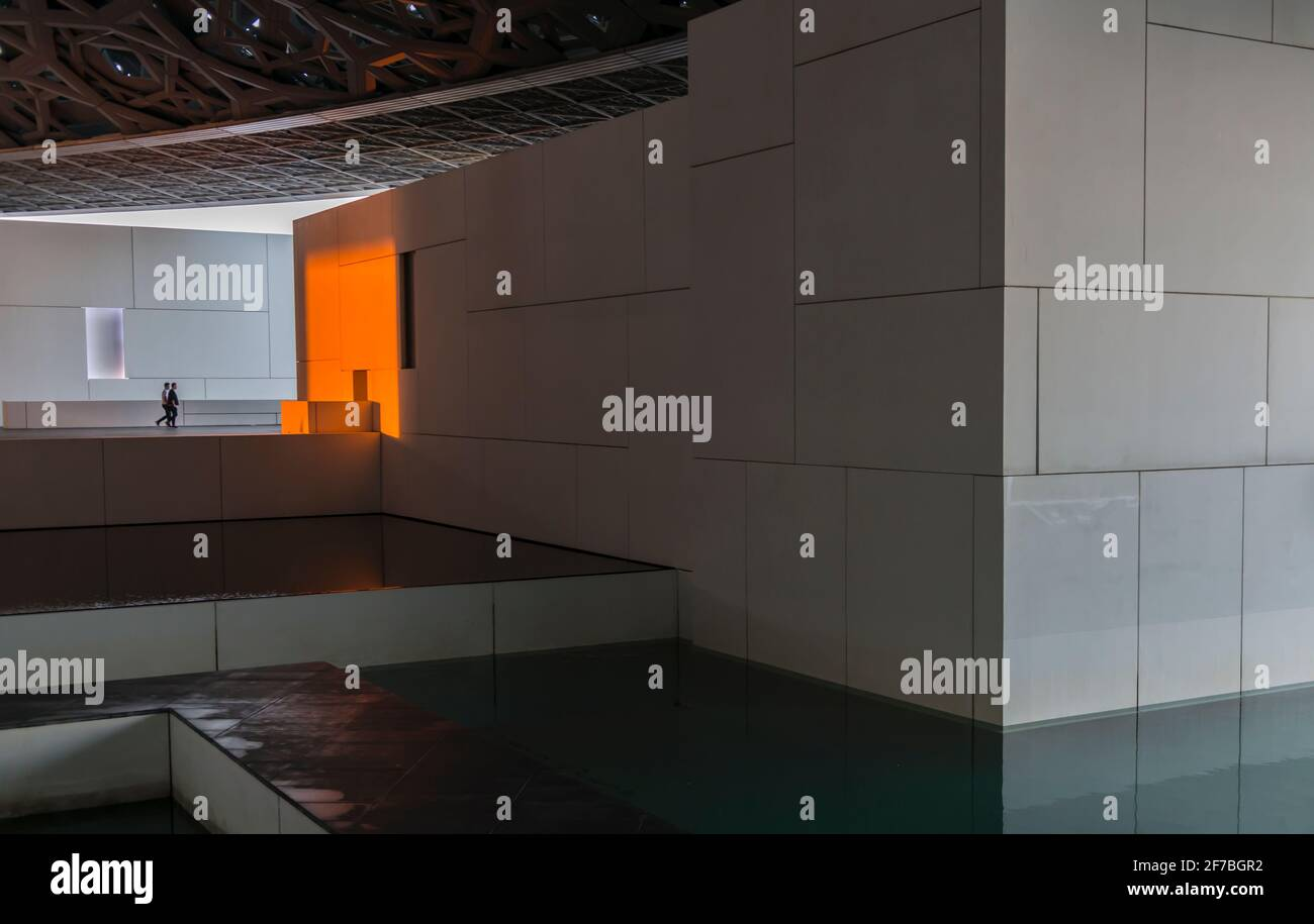 Two men walking in the direction of a white wall changed to orange due to the setting sun. Louvre museum. Abu Dhabi, United Arab Emirates. Stock Photo