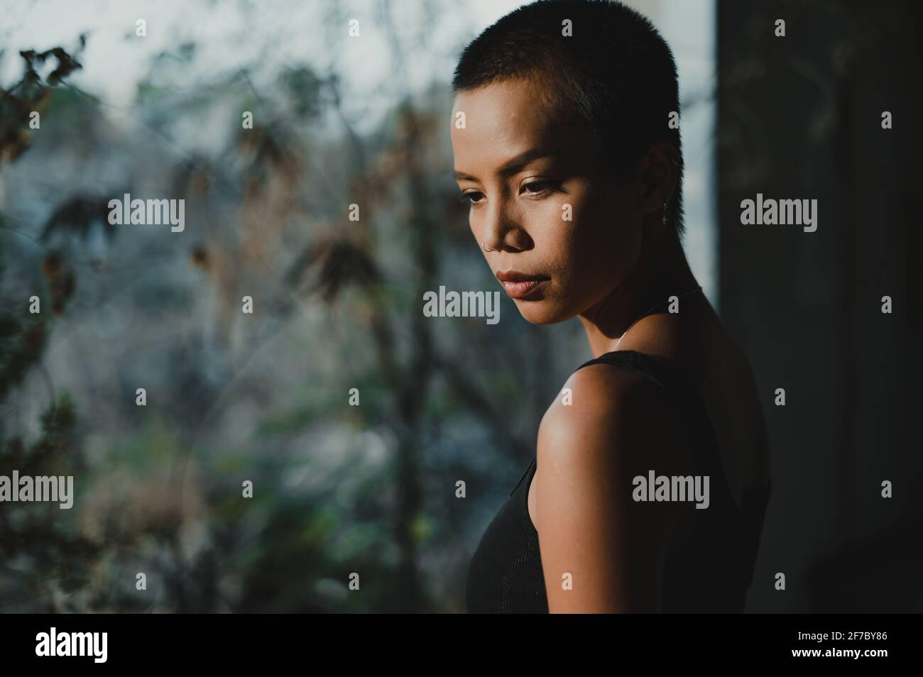Portrait of a young short hair Asian woman standing by a big window looking down, with trees out of focus in the background. Stock Photo