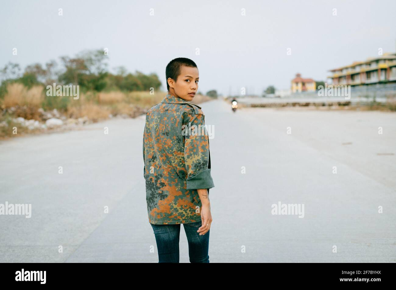 Young short hair Asian woman wearing a sports bra and an army jacket, walking away while looking at the camera over her shoulder. Stock Photo