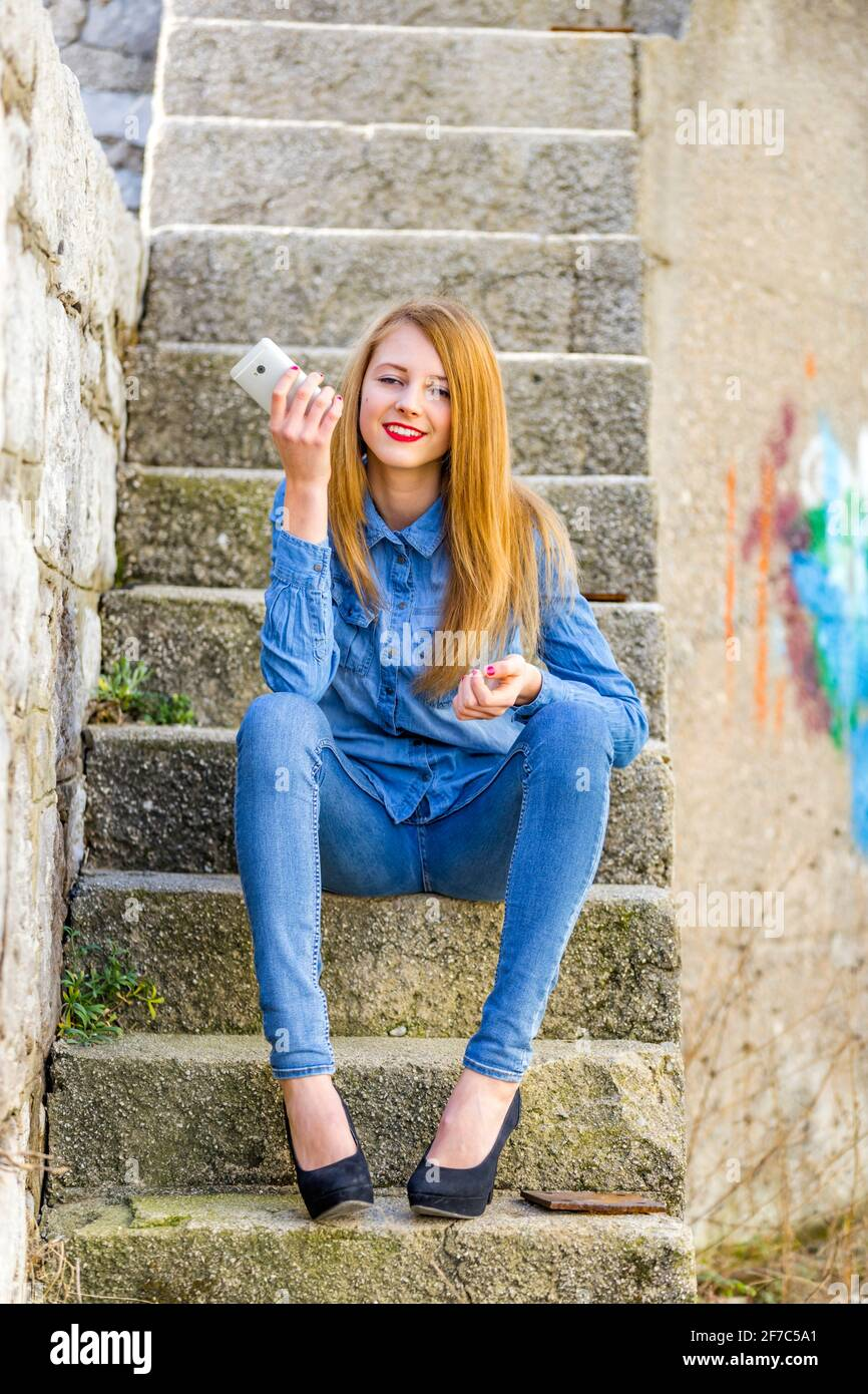 Smiling teengirl blond hair hand holding hold smartphone urban environment staircase steps stairs town denim denims shirt pants clothing legs heels Stock Photo