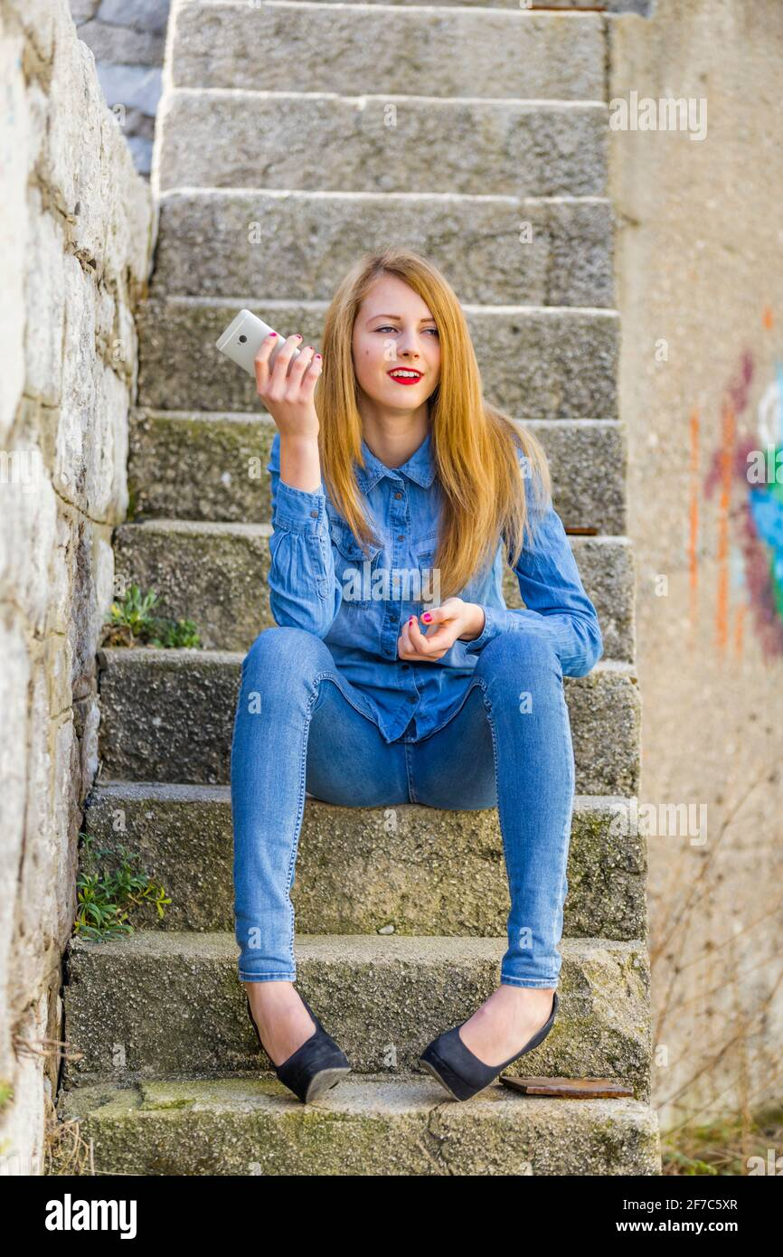 Teengirl cynical looking away hand holding hold smartphone urban environment staircase steps stairs town denim denims shirt pants clothing legs heels Stock Photo