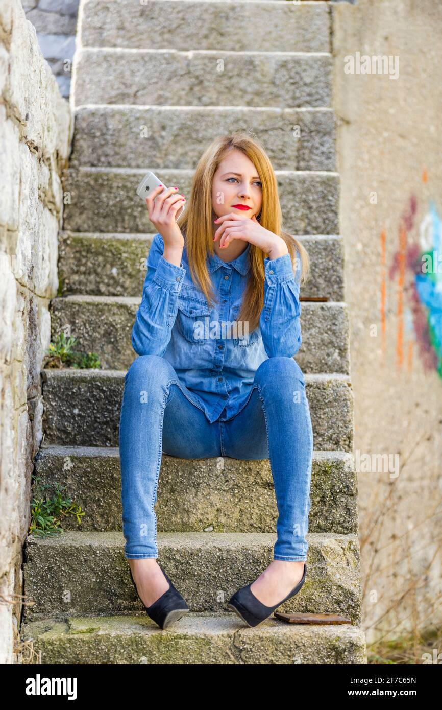 Teengirl looking away aside hand holding hold smartphone urban environment staircase steps stairs town denim denims shirt pants clothing legs heels Stock Photo