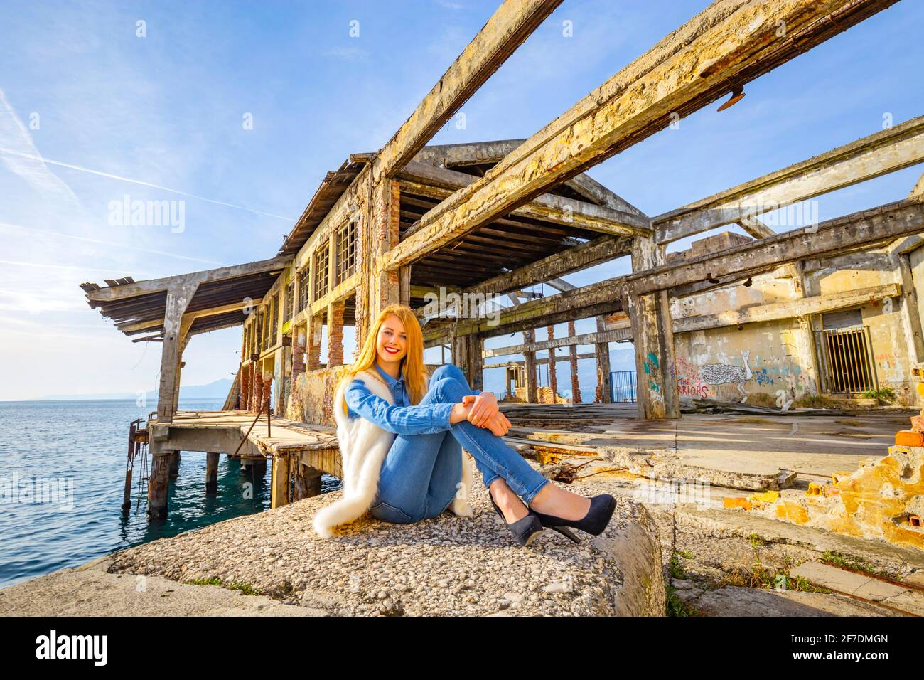 Teengirl blonde smiling at camera seated sitting ground before derelict industrial building framework ex warehouse wearing denim clothing legs heels Stock Photo