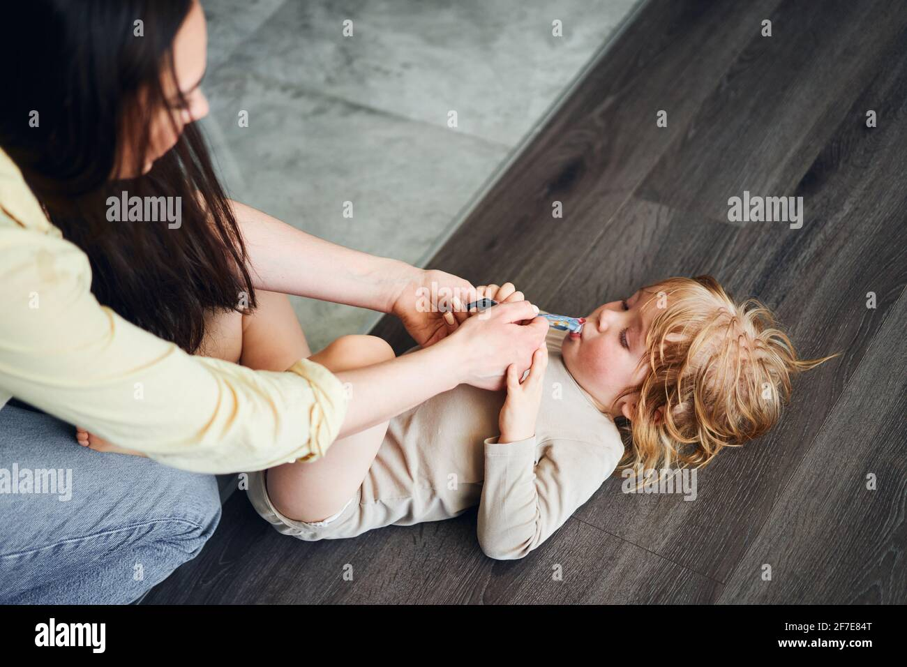woman feeding baby food to her son, who is lying on the floor Stock Photo