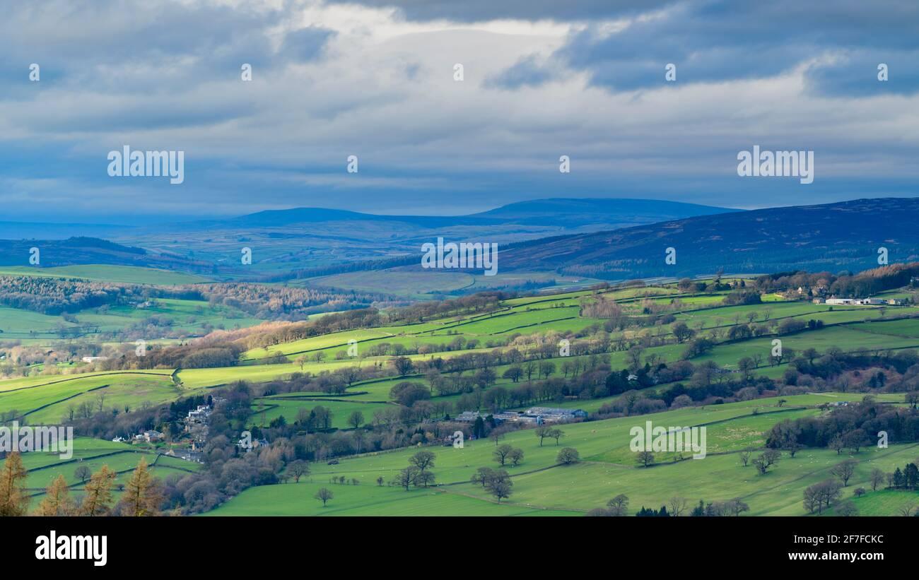 Scenic Wharfedale countryside (green valley, undulating hills, upland fells, sunlight on farmland fields, dramatic sky) - West Yorkshire, England, UK. Stock Photo