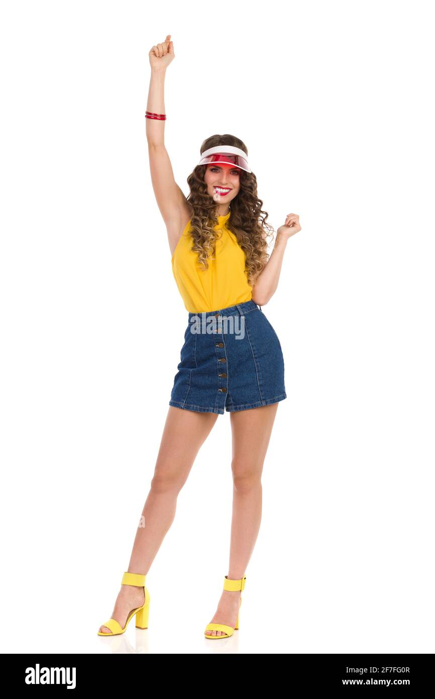 Happy young woman in high heels sandals, jeans mini skirt, yellow top and red sun visor is standing with arm raised and smiling. Front view. Full leng Stock Photo