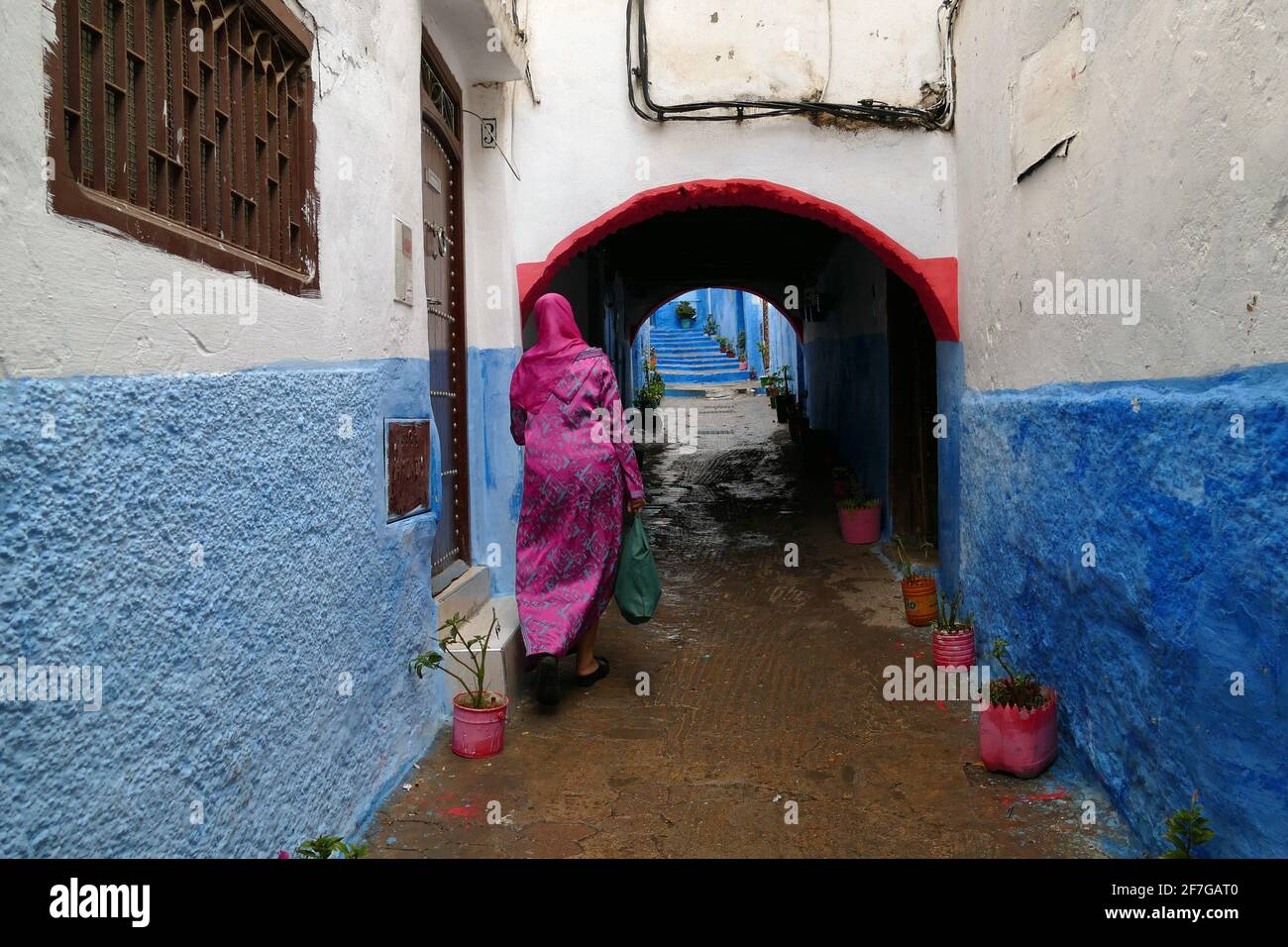 Woman with pink dress walking in a little colorful alley in the medina of Tetouan, North of Morocco, Africa Stock Photo